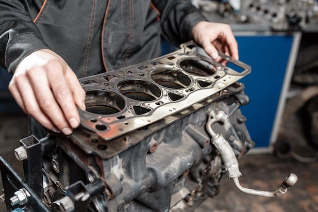 Mechanic fixing oil leaked blown head gasket