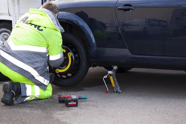 Man installing a spare tire for auto