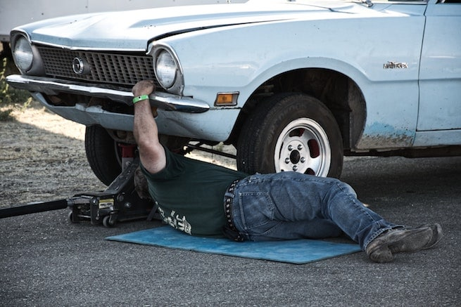 Man fixing failing electrical components on a automobile