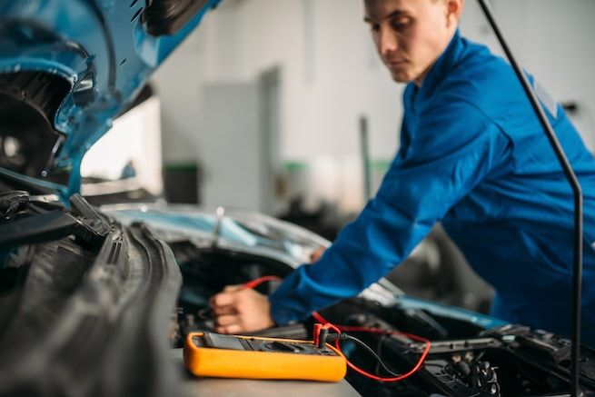 Car electrician performing a multimeter battery inspection