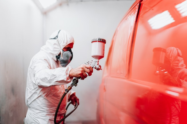 Auto manufacturing industry worker with spray gun with red paint
