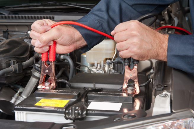 Mechanic connecting car battery charger cables
