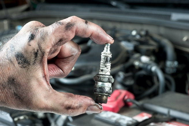 Mechanic replacing bad spark plugs in a car
